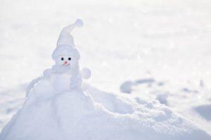 Little white snowman near snowbank