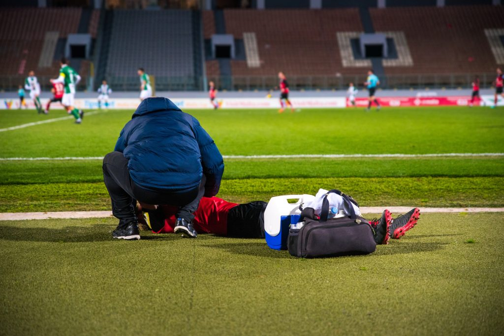 Urgent injury - a sports doctor cares for the football player